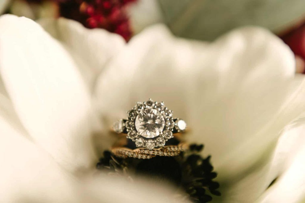 Bride's engagement and wedding ring details in her bridal bouquet