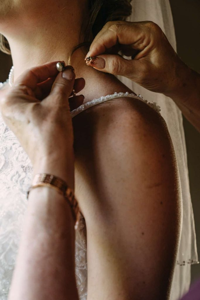 Mother of the bride putting on bride's pearl necklace while she gets ready for her wedding day