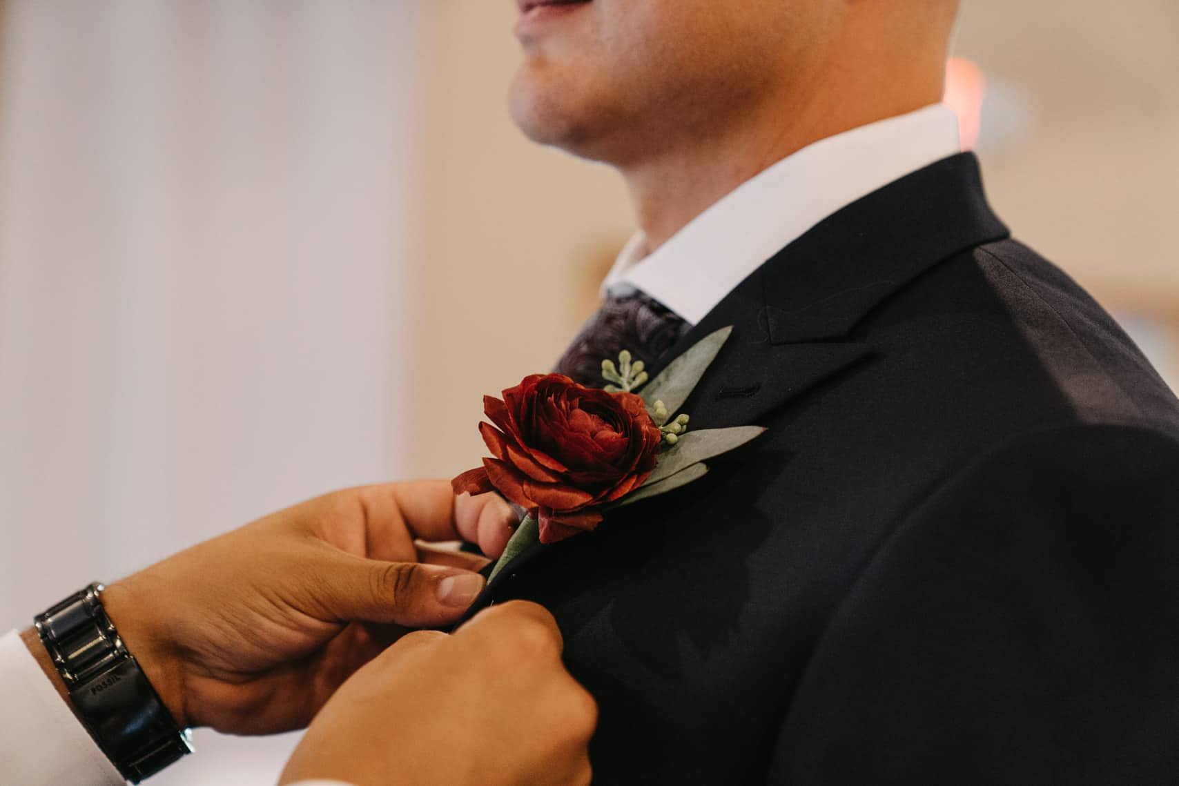 Best man pins boutonniere on the groom for his wedding day