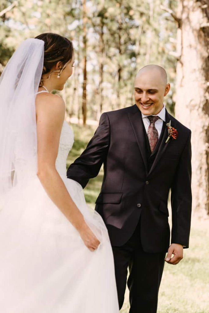 Groom sees bride for the first time with a big smile on his face