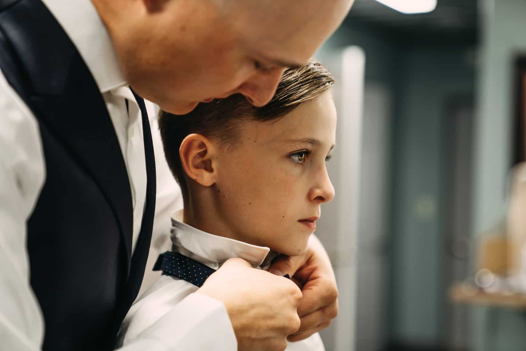 Groom tightens his son's tie in preparation for his wedding day at Woodlands Receptions and Rentals in Piedmont, SD