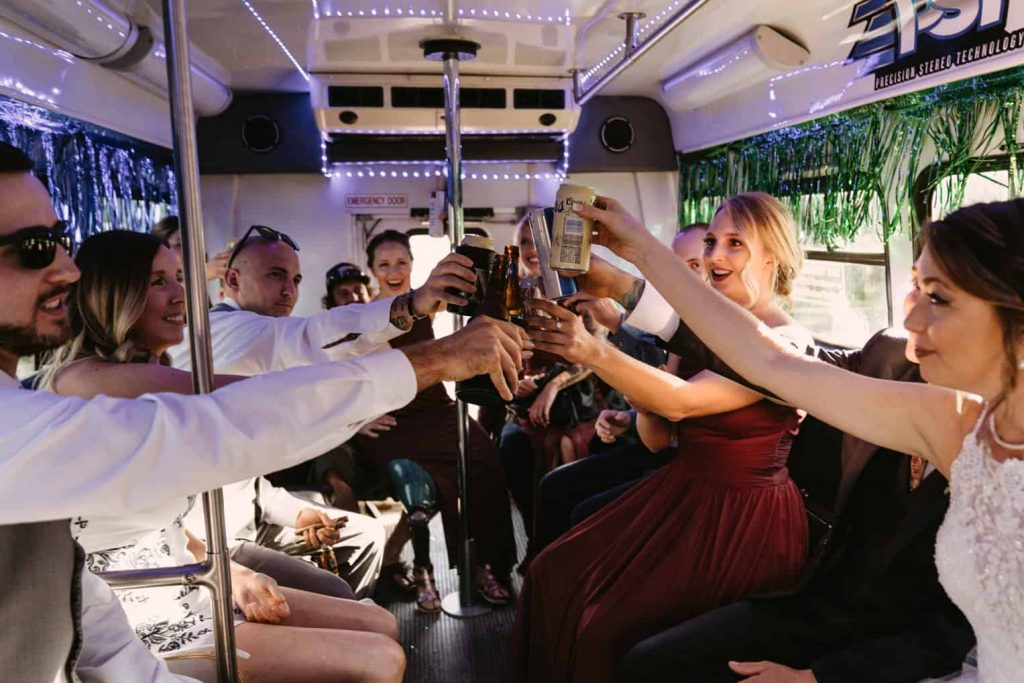 Bride and groom celebrate with a toast with their bridal party on their party bus