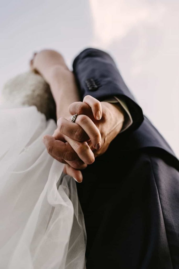 Bride and groom interlacing hands with their rings showing