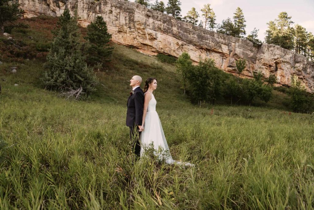 Bride and groom pose back to back in a grassy field