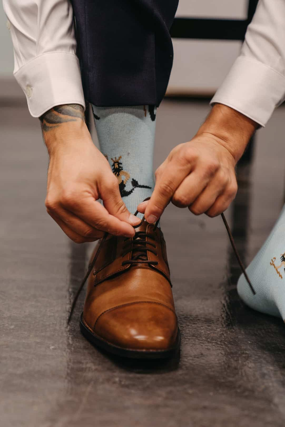 Groom puts on his brown leather shoes