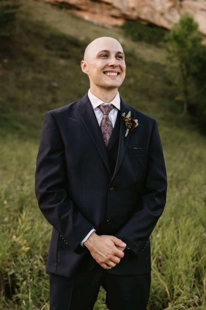 Groom smiling for a photo and staring into the distance