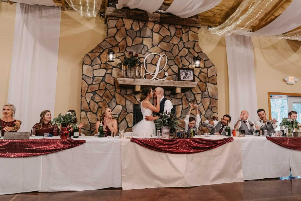 Bride and groom kissing in front of the fireplace surrounded by their bridal party at Woodlands Receptions