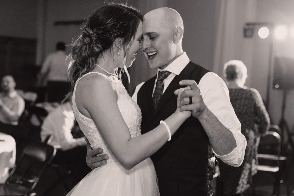 Black and white photo of bride and groom singing and dancing