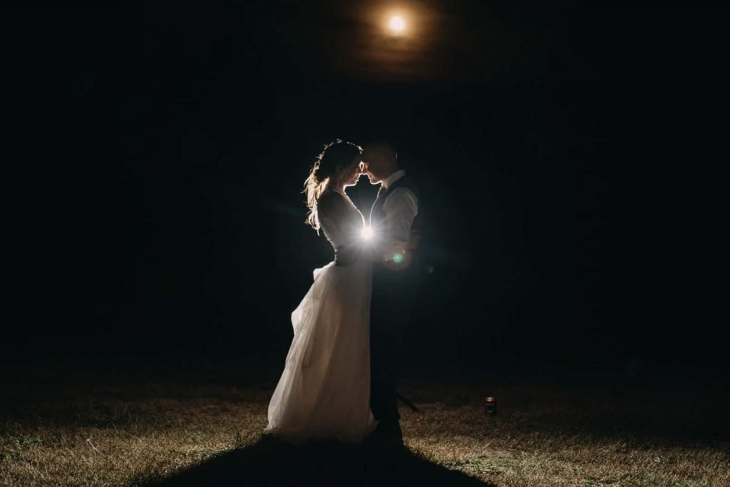 Photo of the bride and groom at night in front of the full moon