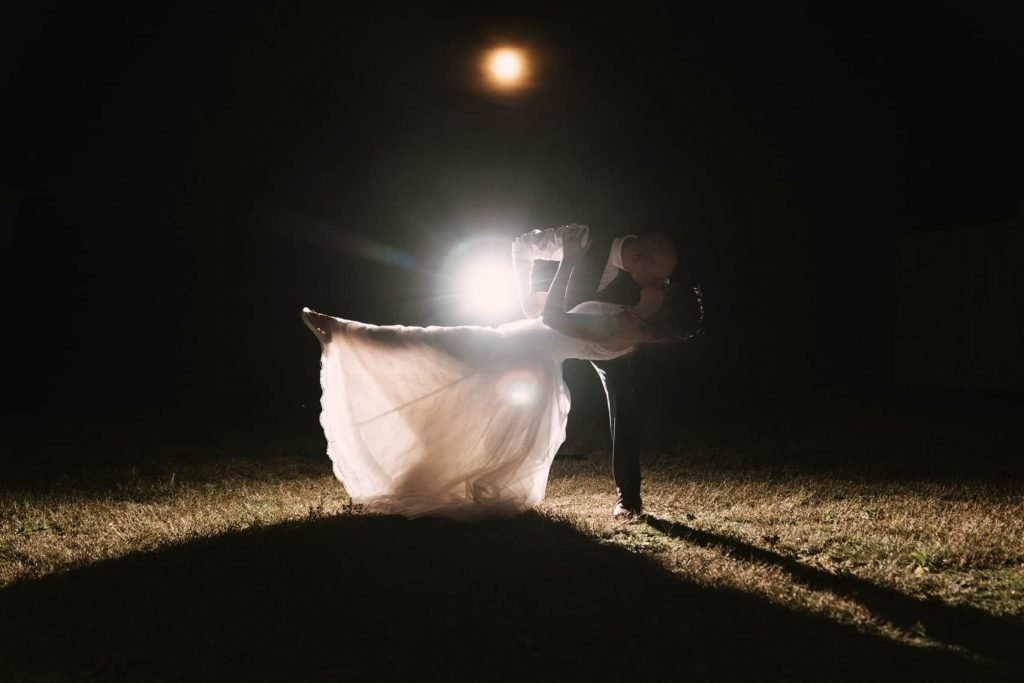 Photo of the groom dipping the bride at night in front of the full moon