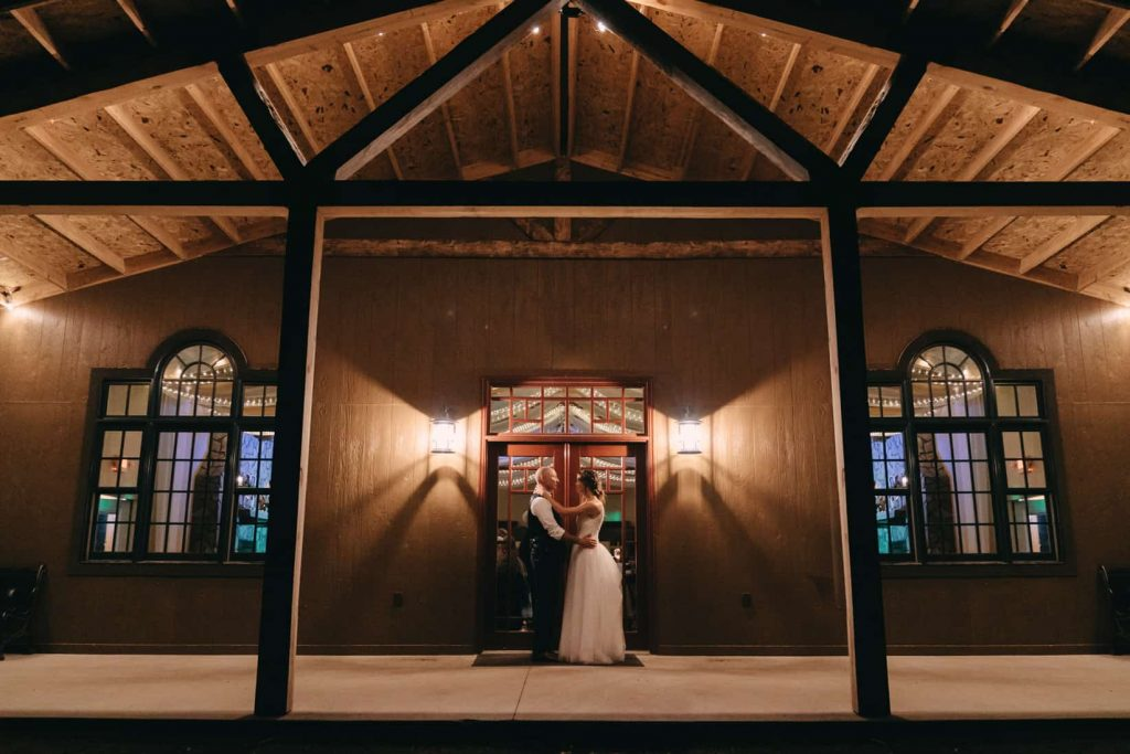 Photo of the bride and groom at night in front of their wedding venue, Woodlands Receptions and Rentals in Piedmont, SD