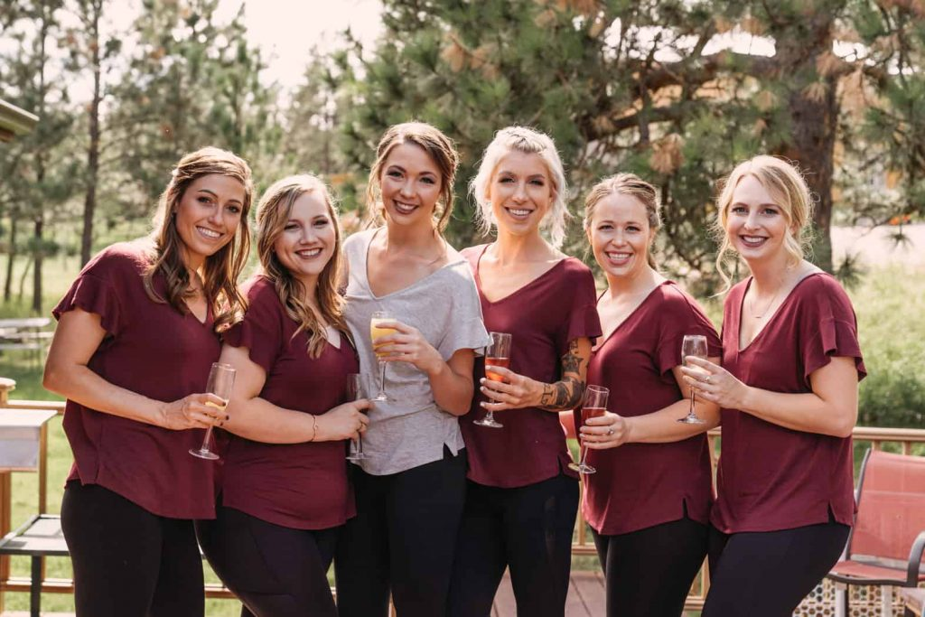Bride poses for a picture with her bridesmaids and mimosas before the wedding day by Paige Weber Photography