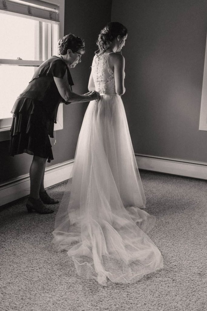 Black and white photo of mother of the bride helps bride put on wedding dress near a large window