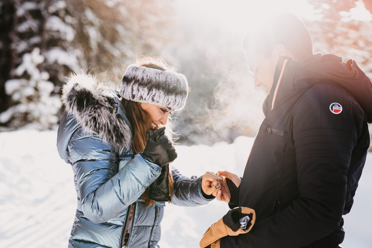 Artistic photo of Fernanda admiring her engagement ring while Julio hold her hand for this sleigh ride proposal in Breckenridge
