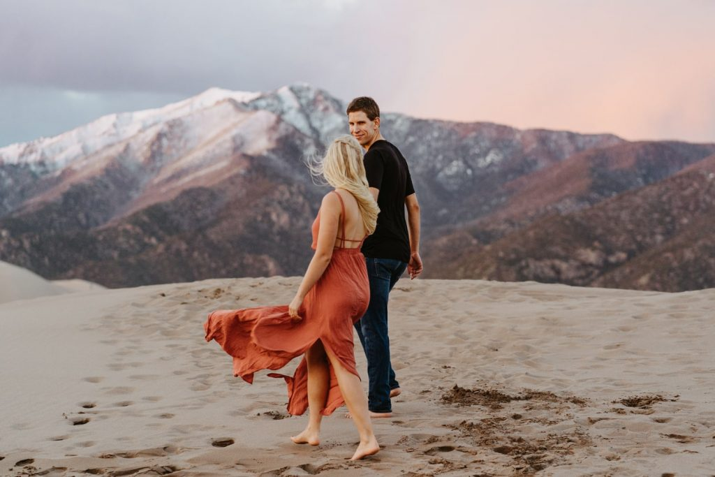 Couple enjoys their first dance barefoot on a sand dune at sunset with snow capped mountains in the background. Great Sand Dunes national park is one of the best places in the state to watch the sunset.