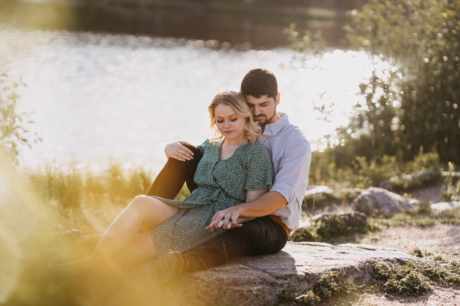 Couple cuddles together in the sunshine next to Sprague Lake in Rocky Mountain National Park. There is no doubt Rocky Mountain National Park is one of the best places to elope in Colorado