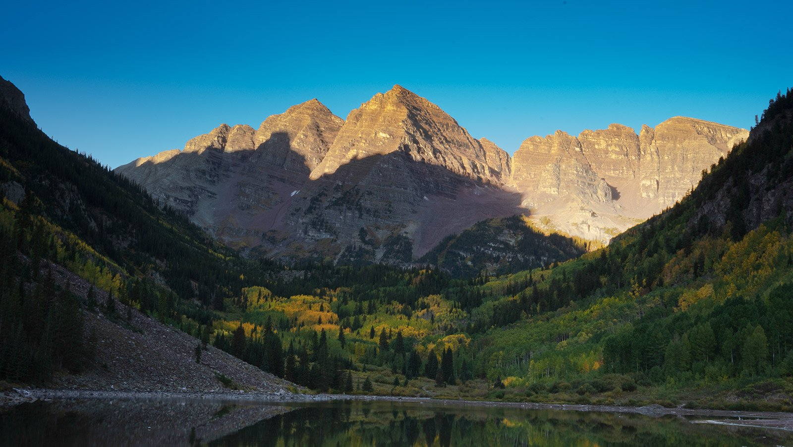 Maroon Bells captured at sunrise during the warm summer months. It's crazy to think this is one of the most photographed mountains in Colorado, but I understand why. Maroon Bells also offers a small space for elopements, and is the perfect spot if you want these majestic mountains in the background for your photos.