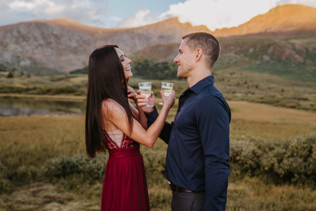 Misty and Cameron toast with a glass of champagne at the base of Mt. Bierdstat after eloping in the mountains at sunset