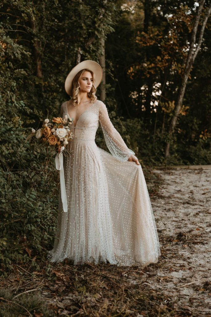 Bride stands in the forest and plays with her dress as she stares into the distance