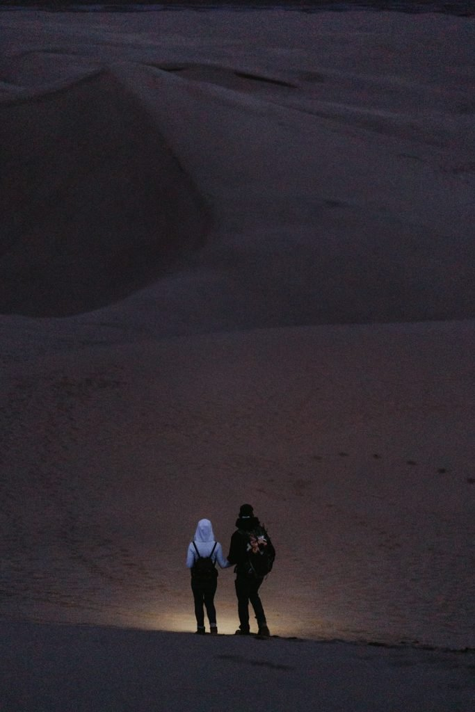 As an elopement photographer, I love guiding couples how to elope in Colorado. Sandy and Adam walk down a tall sand dune at night after their elopement in great sand dunes national park