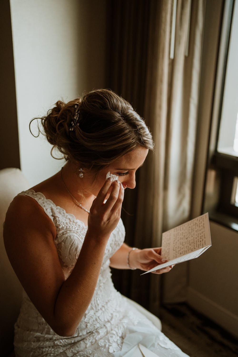 Bride wipes her tears with a tissue as she reads love letter from her groom while getting ready