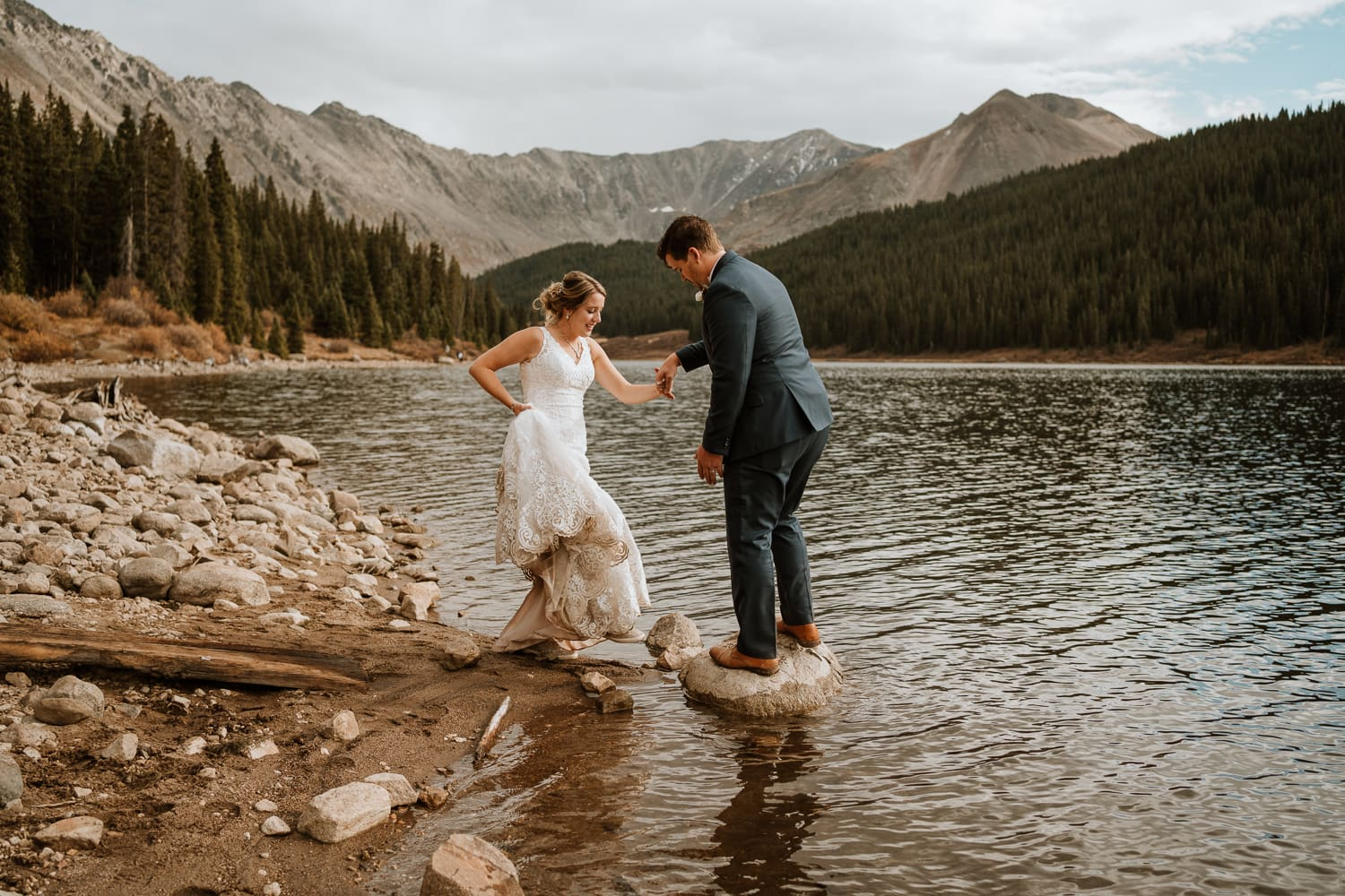 Bride and groom hop onto a rock for their couples portraits during their adventurous Colorado elopement