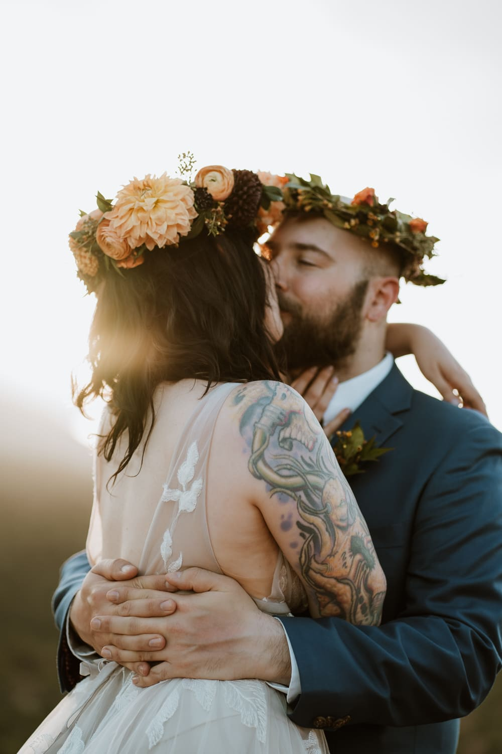 Bride and groom kiss each other during sunset with the sun flaring over her shoulder in Garden of the Gods