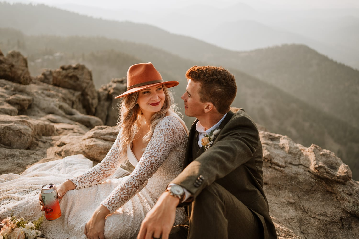 Bride and groom stare into each other's eyes and smile as they drink beer on a mountain top at sunset