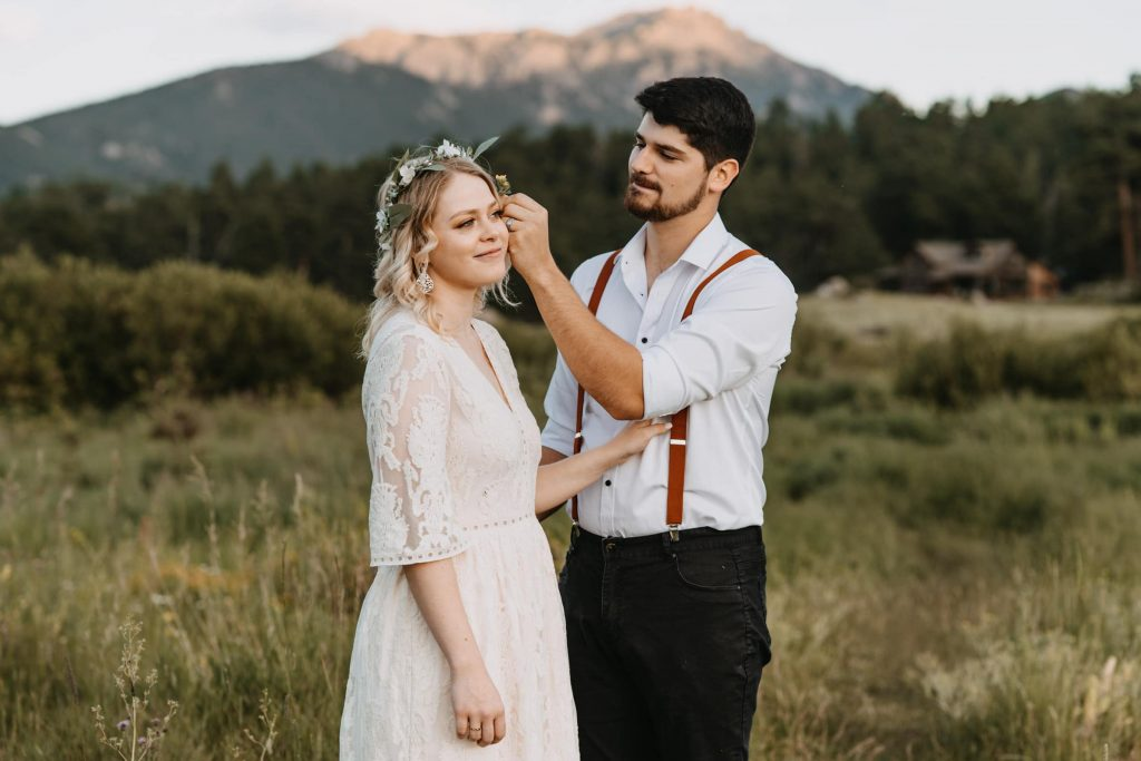 Groom puts a flower in his new brides hair during this elopement in Rocky Mountain National Park. I was honored to help this couple on how to plan an elopement.