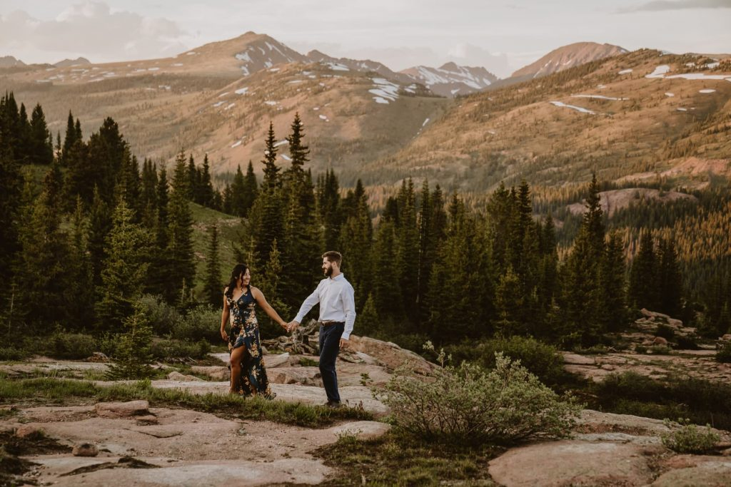 Couple walks along the rocks with towering Colorado mountains behind them. Talk about the best place to elope in Colorado!