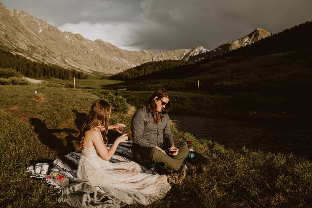 Couple has a picnic next to a lake at the base of a mountain in Colorado. One of the many secret spots I've scouted for the eloping couples I work with.