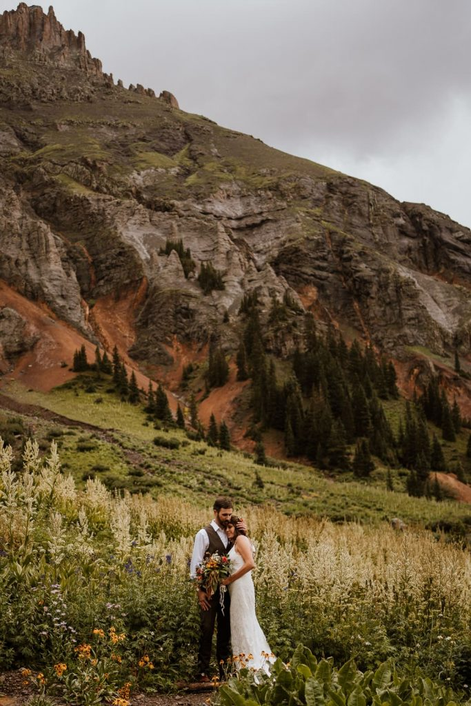 Bride and groom cuddle and take in all the views after sharing their vows in one of the most beautiful places to elope in Colorado - Ouray. In this photo, the mountains rose up behind them and the wildflowers were as tall as they were.
