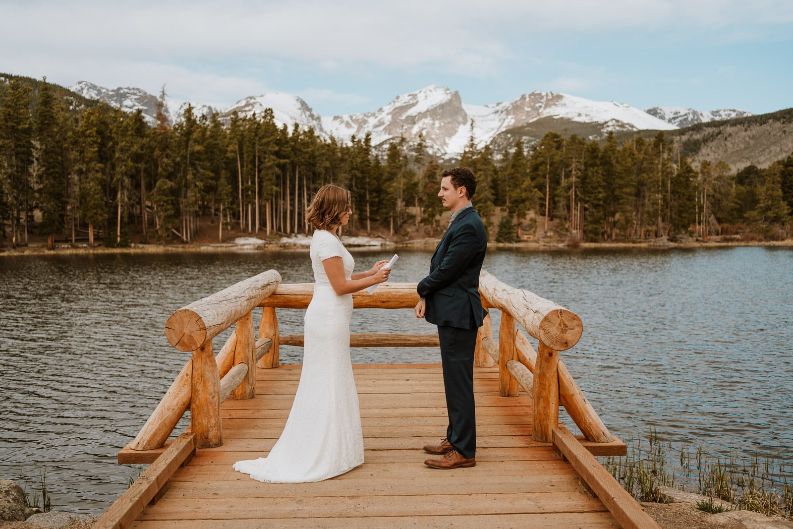 Bride and groom read their elopement vows next to Sprague Lake in Rocky Mountain National Park for their spring elopement in Colorado.