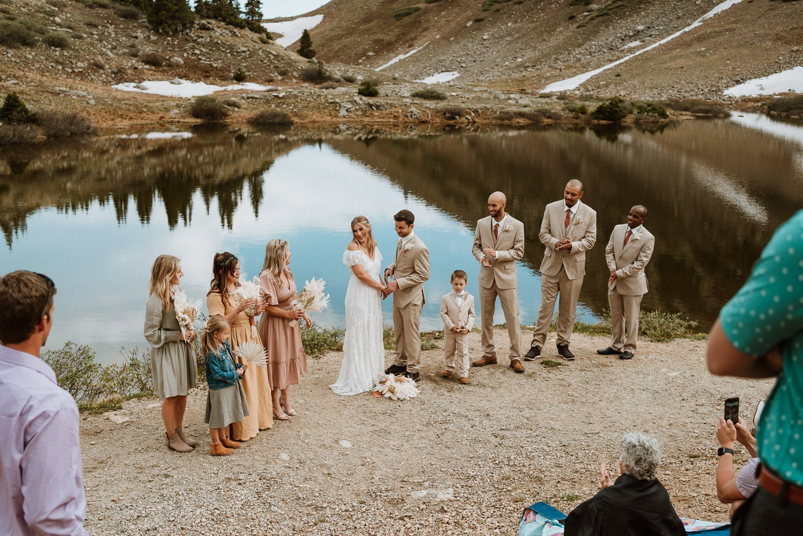 Bride and groom share their vows at Loveland Pass lakes with their bridal party around them for their Colorado elopement. Loveland Pass is one of the best places to elope in Colorado simply for the views and year around access!