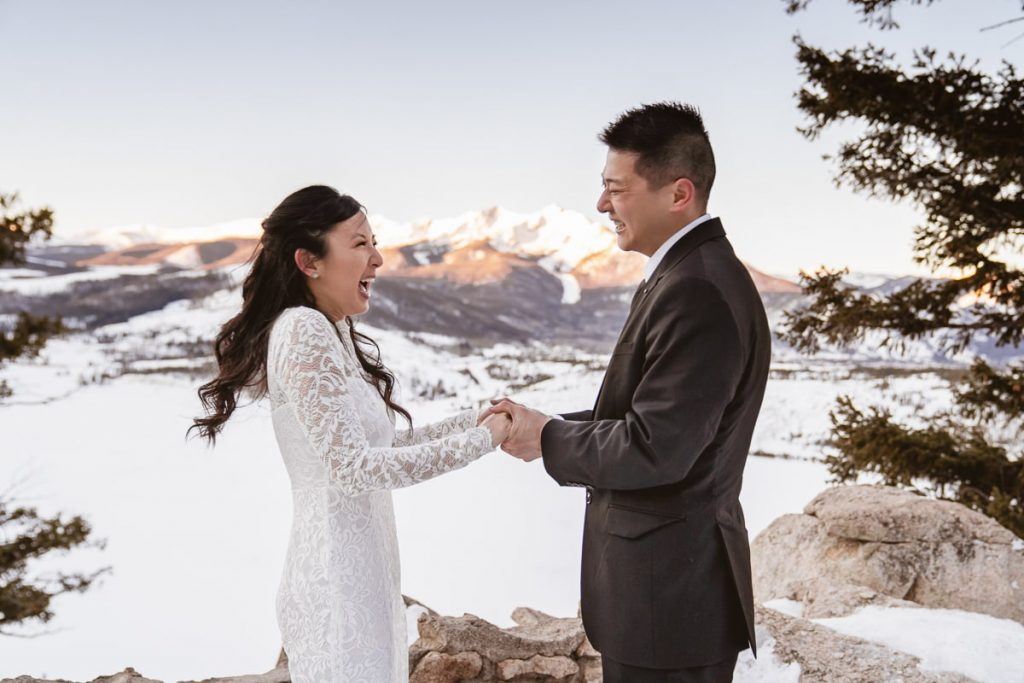 Bride and groom laugh and smile while holding hands with the sunlight lighting up the mountain range behind them at this Sapphire Point elopement