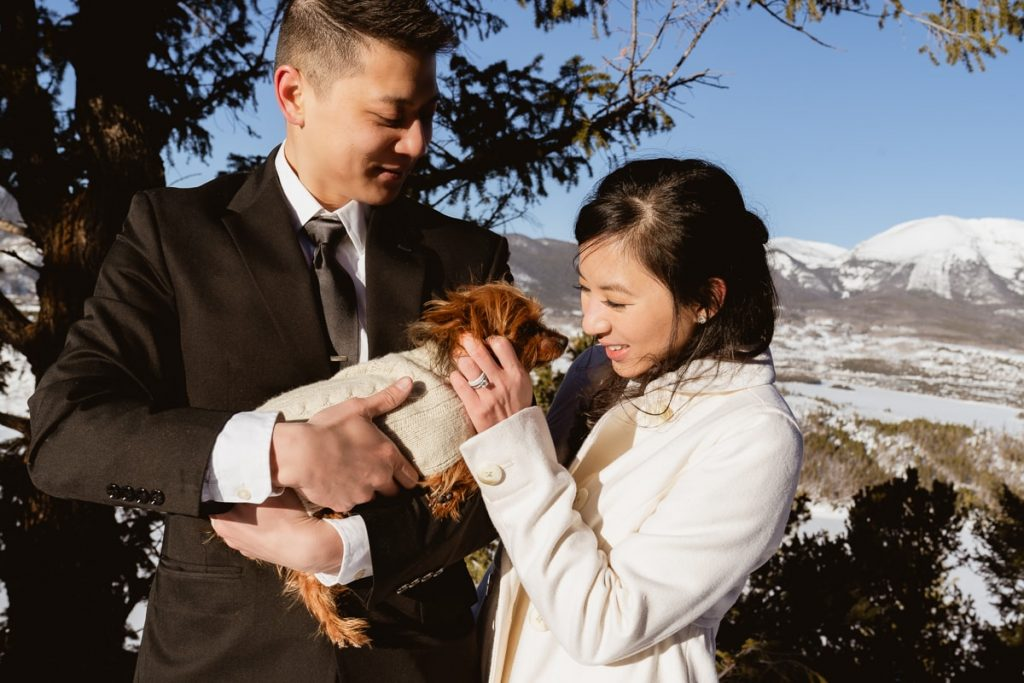 Bride and groom pick up their pup and cuddle her to warm her up during their adventurous sunrise elopement