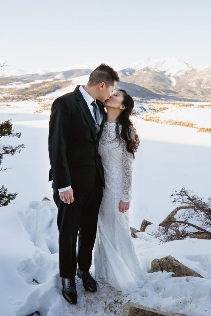 Bride and groom pose and kiss in front of a sunlit mountain range and snow covered lake