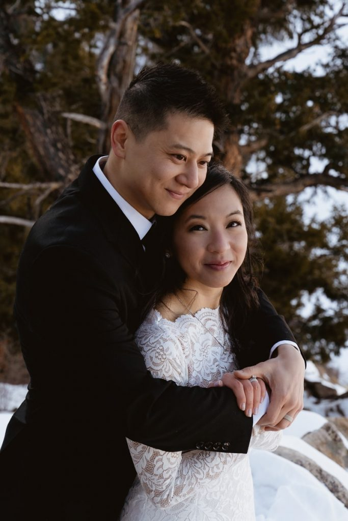 Bride and Groom cuddle up for warmth during their winter Sapphire Point elopement
