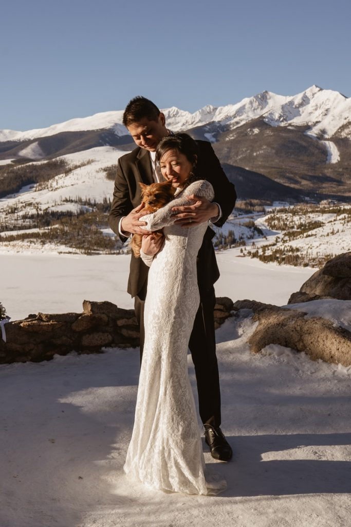 Bride and groom cuddle their dog and bask in the sunlight during this winter Sapphire Point Elopement