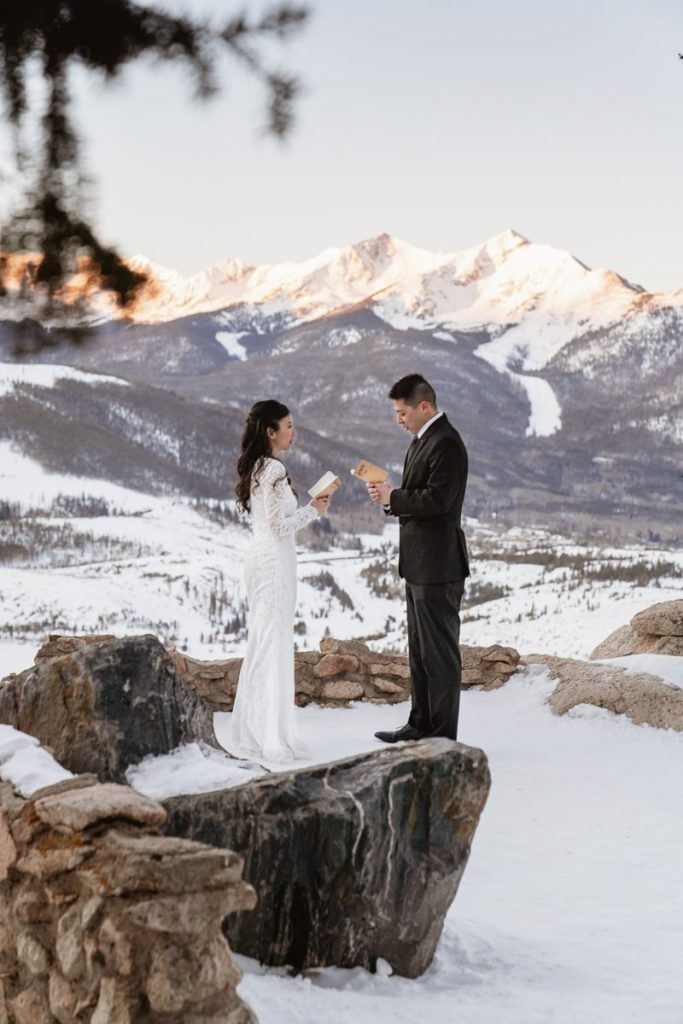 Bride and groom stand in the snowy and say their wedding vows at their winter Sapphire Point Elopement