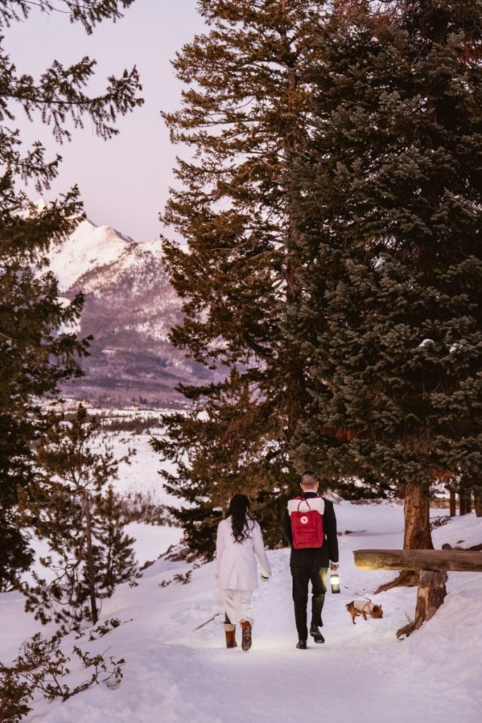 Bride and groom walk down snowy path with their dog to their winter Sapphire Point elopement