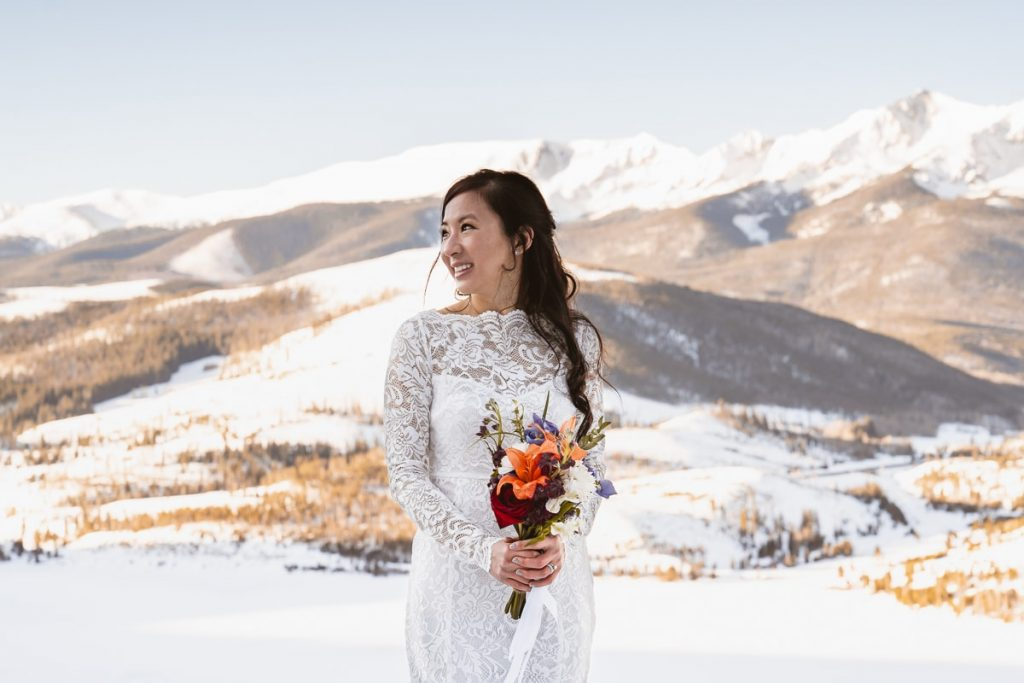 Bride poses in front of mountain during sunrise