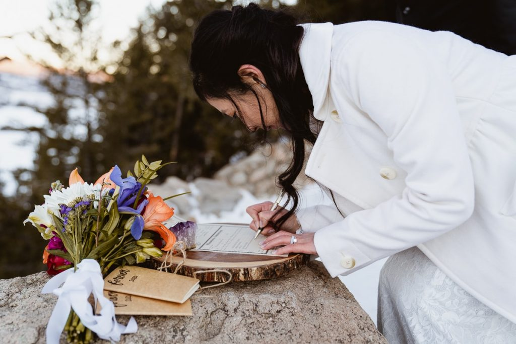 Bride signs her marriage license on a piece of wood at her winter Sapphire Point elopement