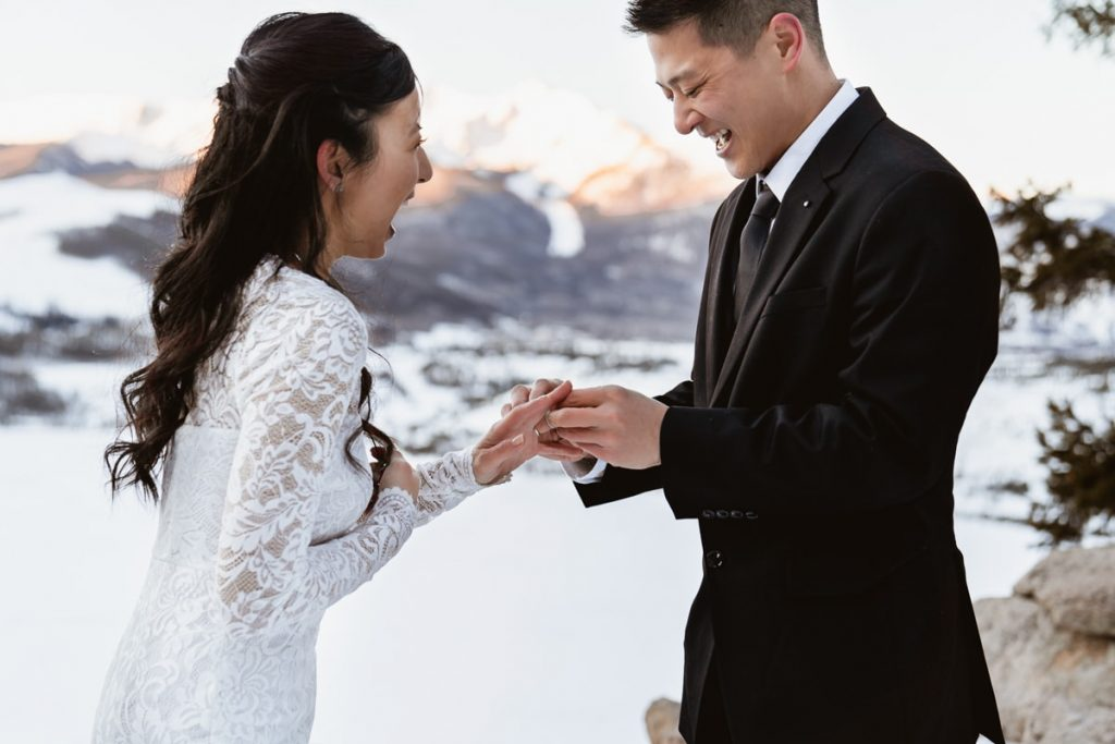 Bride and groom smile and laugh as they put on their wedding bands for their sunwise winter Sapphire Point elopement