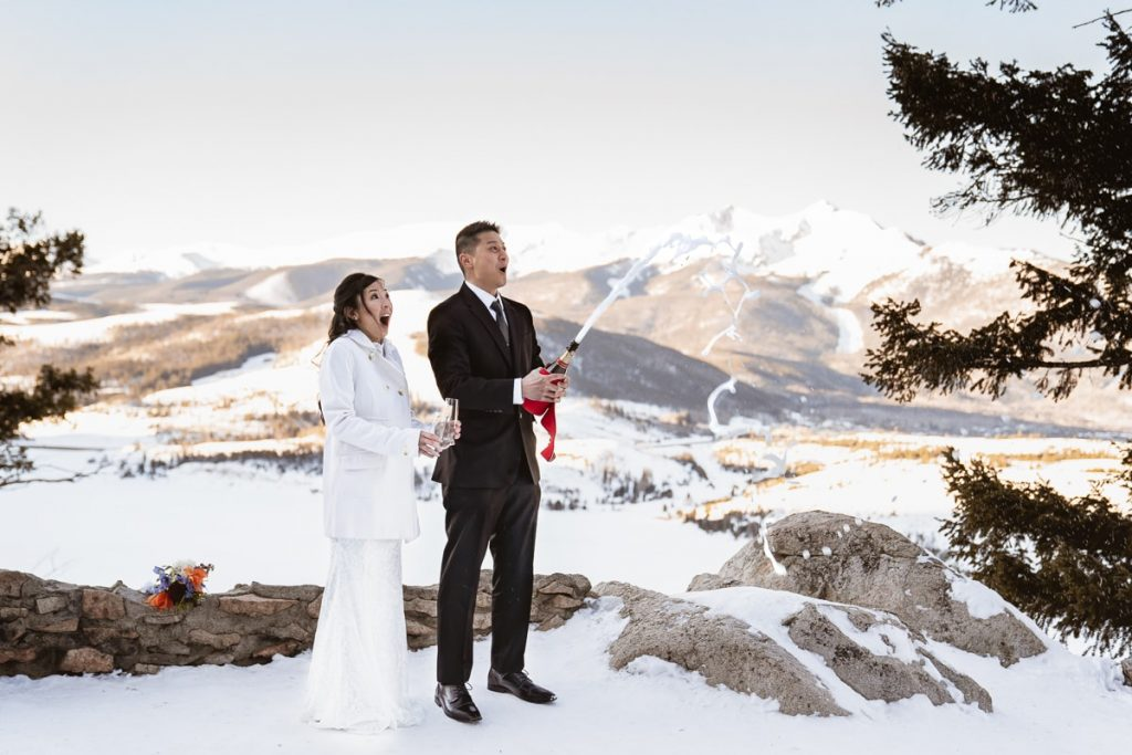 Bride and groom pop champagne to celebrate eloping during sunrise at Sapphire Point Overlook in Colorado, just outside of Breckenridge and Dillon