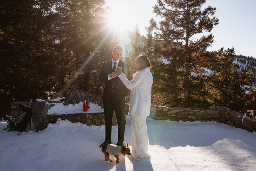 Bride and groom toast as they drink champagne in the sunlight for their winter Sapphire Point Elopement