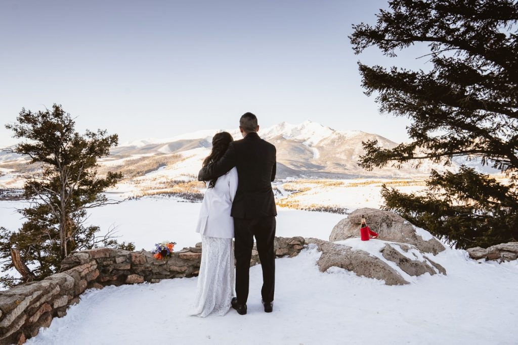 Bride and groom enjoy hug and enjoy the view of the sunrise over the mountains and the snow covered Dillon reservoir during their Sapphire Point elopement