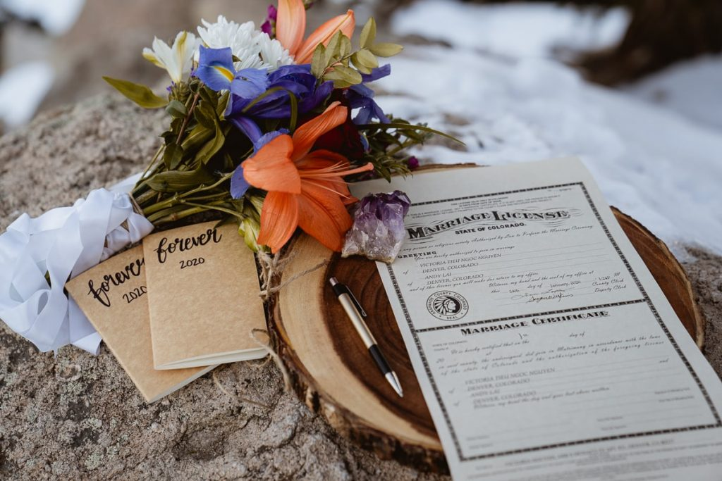 Detail shots of the bridal bouquet, vow books, and the marriage license before the bride and groom sign it