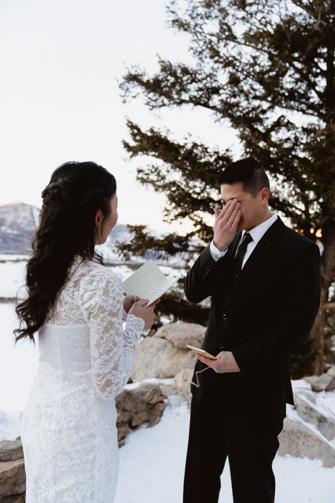Groom wipes tears from face as they say their vows during their winter Sapphire Point elopement
