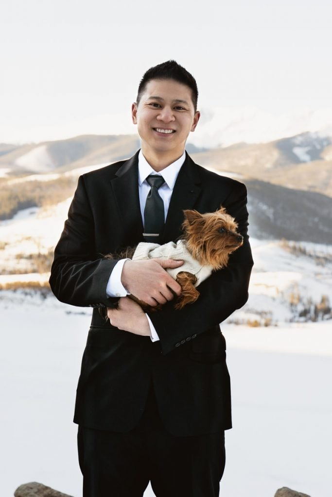 Groom poses with his dog, Izzy, for their winter Sapphire Point elopement